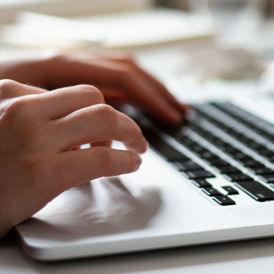Image of hands hovering above a laptop keyboard